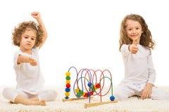 Девушки при деревянная игрушка давая большие пальцы руки вверх Стоковое фото RF