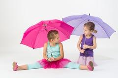 Девушки при зонтики смотря друг к другу Стоковые Фотографии RF
