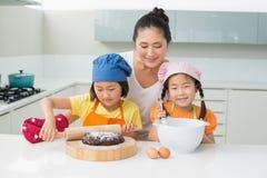 Девушки при их мать подготавливая печенья в кухне Стоковые Изображения