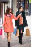 Девушки при пакеты смотря окна магазина пока ходящ по магазинам Стоковые Изображения