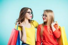 2 девушки при улыбка смотря один другого Молодость, покупки, мода Стоковые Фотографии RF