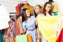 Девушки при хозяйственные сумки выбирая одежды Стоковые Фотографии RF