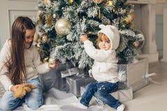 2 девушки при шляпа santa кладя перед рождественской елкой Стоковое Фото
