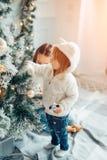 2 девушки при шляпа santa кладя перед рождественской елкой Стоковая Фотография