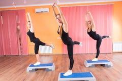 Девушки протягивая и балансируя на аэробных шагах Стоковые Фотографии RF