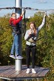 Девушки проходят полосу препятствий в взбираясь парке Стоковая Фотография