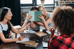 Девушки работая пока сидящ на таблице в домашнем офисе Стоковые Изображения RF