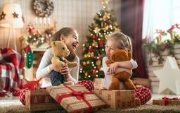Девушки раскрывая подарки рождества стоковые изображения