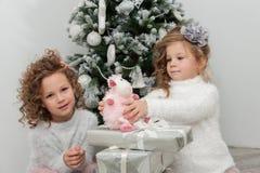 Девушки ребенка с подарками приближают к рождественской елке Стоковые Фотографии RF