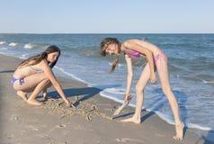 Девушки рисуя в песке на пляже в солнце лета Стоковые Изображения RF