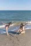 Девушки рисуя в песке на пляже в солнце лета Стоковое фото RF