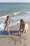 Девушки рисуя в песке на пляже в солнце лета Стоковые Изображения