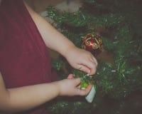 Девушки рук украшают конец-вверх рождественской елки Стоковые Фото