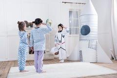 Девушки салютуя к мальчику в костюме астронавта Стоковая Фотография RF