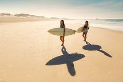 Девушки серфера идя на пляж Стоковые Изображения