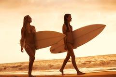 Девушки серфера на пляже на заходе солнца в Гаваи Стоковая Фотография RF