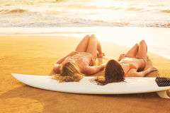 Девушки серфера на пляже на заходе солнца в Гаваи Стоковые Изображения