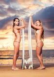 Девушки серфера на пляже на заходе солнца в Гаваи Стоковое Изображение RF