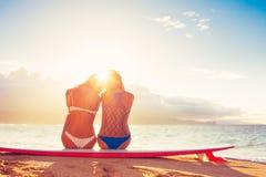 Девушки серфера на пляже на заходе солнца Стоковые Фото