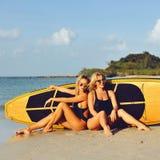 Девушки серфера представляя с surfboard на пляже Стоковая Фотография RF