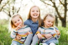 3 девушки сестры играя на зеленом парке внешнем Стоковые Изображения RF