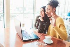 Девушки сидят в кафе и беседуют с кто-нибудь Вероятно оно ` s их третий друг который может ` t быть с ними Молодые стоковое фото
