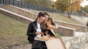 2 девушки сидят в парке и едят очень вкусную большую пиццу с цыпленком и грибами акции видеоматериалы