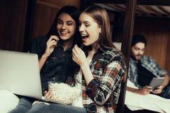 Девушки сидят на кровати и смотреть фильм совместно стоковые изображения