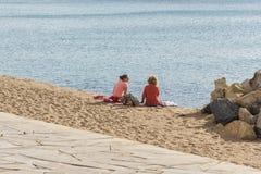 2 девушки сидят на пляже около воды и говоря b Стоковые Фотографии RF