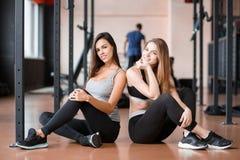 2 девушки сидят на поле в спортзале и усмехаются Стоковое Изображение RF