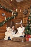 2 девушки сидят на поле на предпосылке деревянной стены около рождественской елки Стоковые Изображения RF