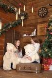 2 девушки сидят на поле на предпосылке деревянной стены около рождественской елки Стоковая Фотография