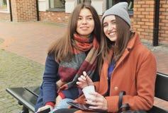 2 девушки сидят на стенде и усмехаются Стоковые Фотографии RF