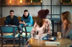 Девушки сидят на таблице и развевая парнях Стоковое Изображение RF