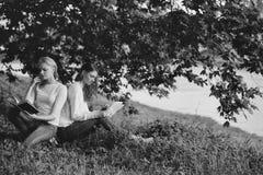 2 девушки сидят на траве Стоковые Фотографии RF