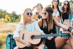 Девушки сидят на хоботе с гитарой Стоковые Фотографии RF