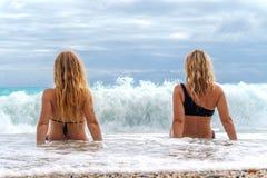 2 девушки сидя на пляже около брызга моря от большой волны Стоковое Изображение