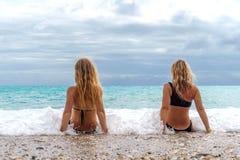 2 девушки сидя на пляже около брызга моря от большой волны Стоковые Фото