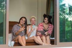 3 девушки сидя на телефонах клетки пользы кровати умных и беседовать молодой женщины планшета счастливом усмехаясь онлайн внутри Стоковое фото RF