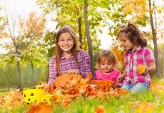 Девушки сидят в парке осени вместе с тыквами Стоковые Изображения RF