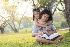 Девушки сидят и чтение Стоковые Фото