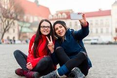 Девушки сидя в улице принимая selfie Стоковое Изображение