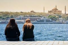 Девушки сидя на береговой линии, Стамбуле, Турции Стоковые Фото
