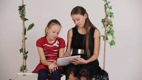 Девушки сидя на качании с цифровой таблеткой акции видеоматериалы