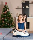 Девушки сидя на кресле около рождественской елки и настоящих моментов Стоковые Фотографии RF