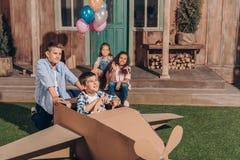 Девушки сидя на крылечке пока мальчики играя с самолетом картона Стоковые Изображения