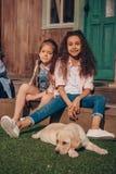 Девушки сидя на крылечке с милым щенком labrador Стоковое фото RF