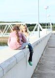 Девушки сидя на перилах запруды Стоковые Фотографии RF