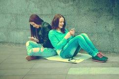 Девушки сидя на улице Стоковые Изображения RF
