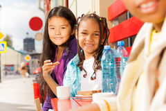 Девушки сидя снаружи на красных стендах в кафе Стоковая Фотография RF